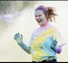 "Emily Quillen jogs through a cloud of cornstarch during a 5K ""color run"" in Sacajawea Park on Saturday afternoon. The run, which attracted about 50 participants, served as a fundraiser for Park High student members of Family, Career and Community Leaders of America to attend a national competition in Nashville this summer. Quillen is one of the student's bound for Nashville."